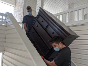 College Movers in Boston carrying dresser for home move